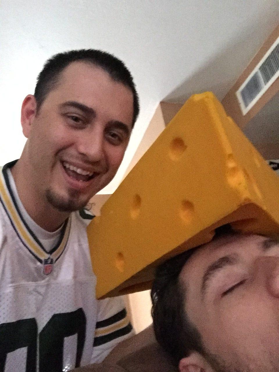 Brandon selfie with Blake asleep wearing Green Bay Packers cheesehead
